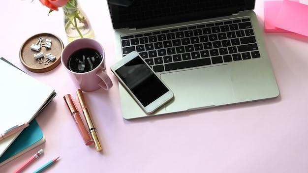 Vue de dessus de la table femme avec accessoires et cosmétique femme mettant dessus. ordinateur portable, smartphone, post-it, tasse à café, cosmétique, cahier, clip et plante en pot à plat ensemble sur table rose.
