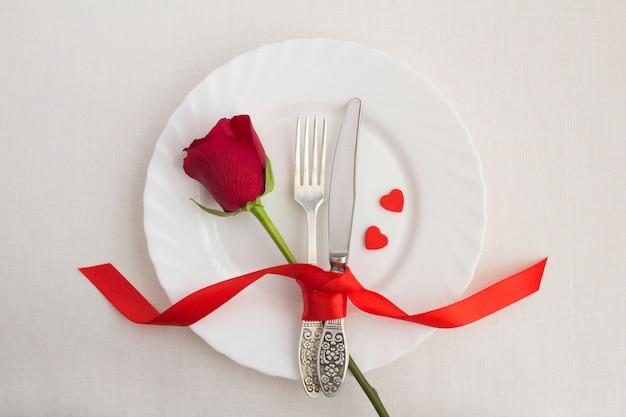 Vue de dessus de la table de fête avec rose rouge, fourchette et couteau sur la plaque blanche