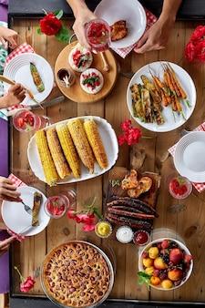 Vue de dessus sur une table à manger, décorée de fleurs, avec vaisselle et nourriture. pique-nique dans la cour entre amis ou voisins, souper en famille.