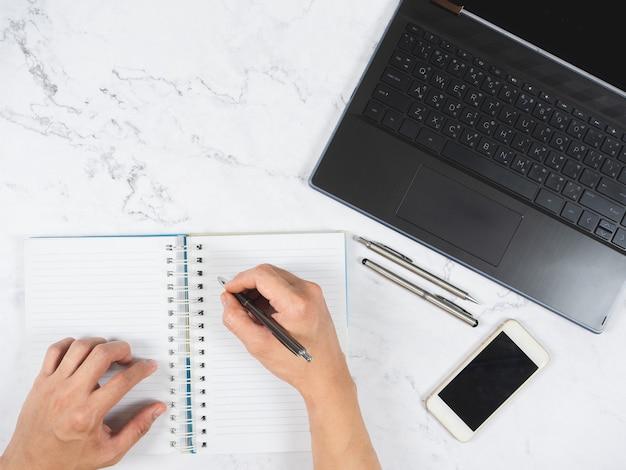 Vue de dessus de la table en marbre de l'espace de travail écrivant à la main sur un ordinateur portable avec un stylo et un espace pour téléphone portable et ordinateur portable
