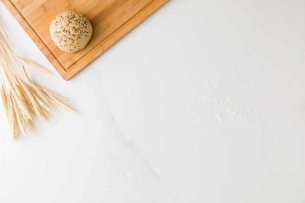 Vue de dessus d'une table en marbre avec un pain reposant dans une planche de bois, du blé et de la farine avec un espace pour le texte