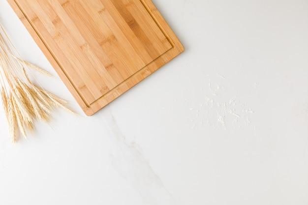 Vue de dessus d'une table en marbre avec une planche de bois, du blé et de la farine avec un espace pour le texte