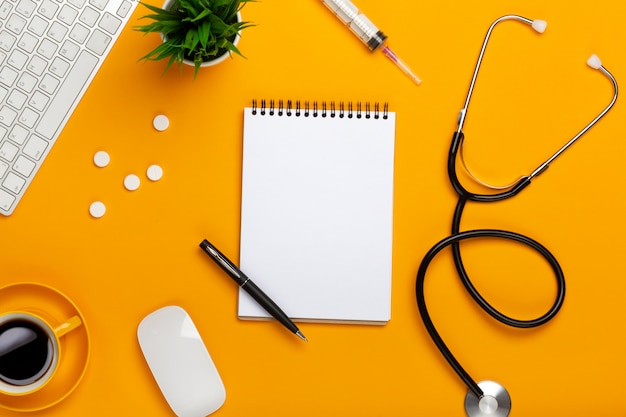 Vue de dessus d'une table de médecin avec un bloc-notes et un stylo stéthoscope, un clavier, une ordonnance et des pilules