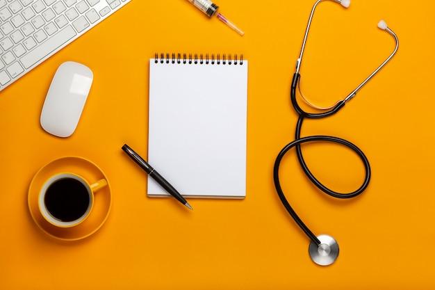 Vue de dessus d'une table de médecin avec bloc-notes et stylo stéthoscope