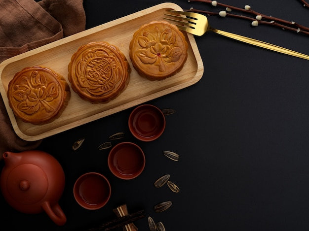 Vue de dessus de la table moderne sombre avec service à thé, gâteaux de lune sur plateau en bois, décoration et espace de copie. le caractère chinois sur le gâteau de lune représente