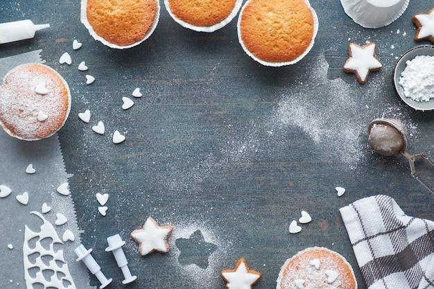 Vue de dessus de la table avec des muffins saupoudrés de sucre et des biscuits étoile de noël sur noir