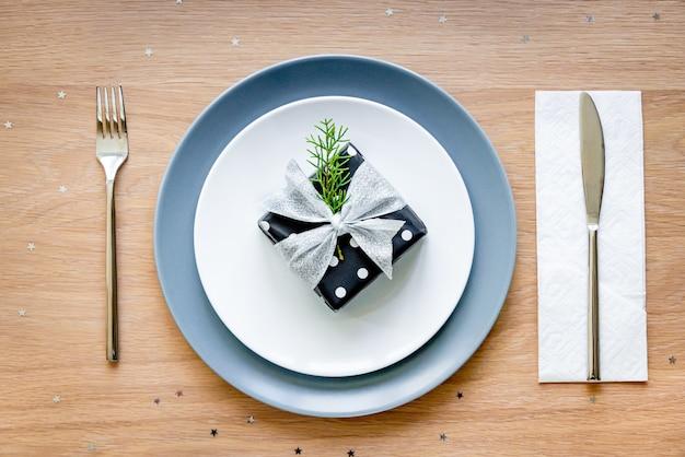 Vue de dessus de la table de noël. un coffret cadeau dans une assiette.