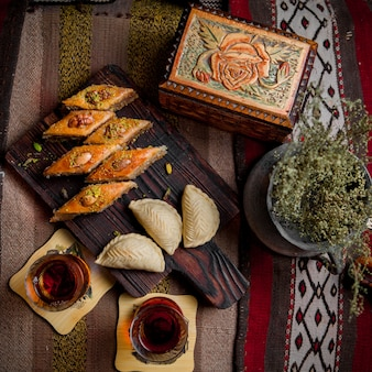 Vue de dessus table sucrée avec baklava et shekerbura et verre de thé en planche à découper