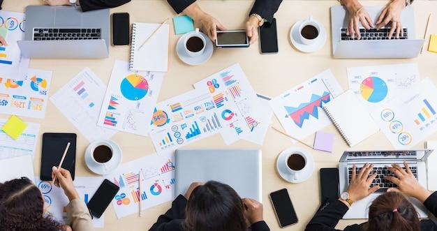 Vue de dessus de table d'une table de conférence en bois avec différents graphiques et papiers graphiques dessus et six mains de femmes d'affaires travaillant sur tablette et ordinateur portable autour de la table. concept pour réunion d'affaires.
