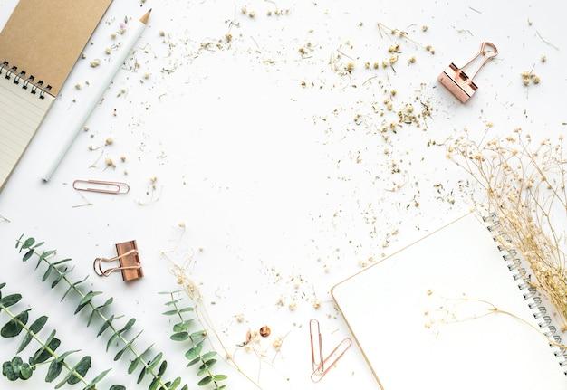 Vue de dessus de la table de travail avec des accessoires de maquette et des fleurs sèches.