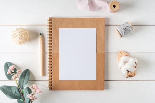 Vue de dessus de la table de travail blanche avec cahier de papier vierge, coton nature. feuille verte à plat, fleurs, trombones en papier doré. bloc-notes et stylo.