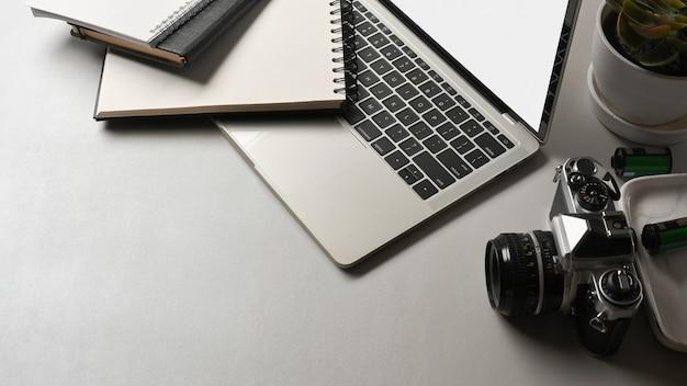 Vue de dessus de la table de travail avec cahiers de caméra portable et espace de copie dans la salle de bureau