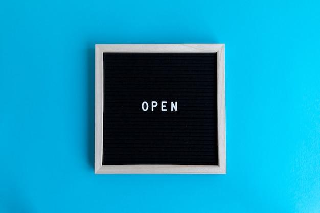 Vue de dessus d'un tableau noir avec un cadre blanc avec un massage ouvert sur fond bleu