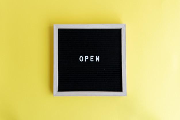 Vue de dessus d'un tableau noir avec un cadre blanc avec un massage ouvert sur fond jaune