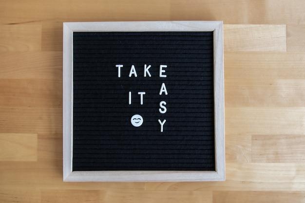 Vue de dessus d'un tableau noir avec une citation facile et un joyeux emoji dessus sur une table en bois