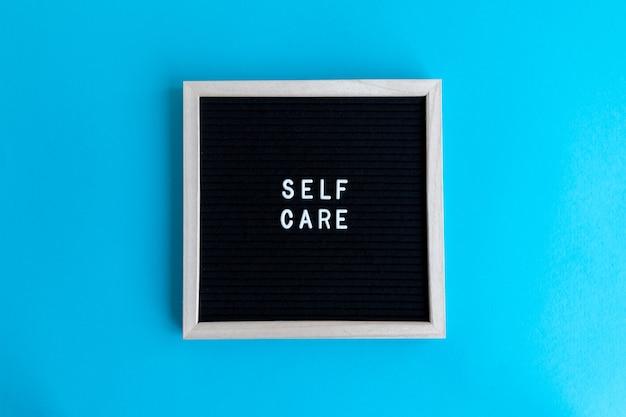 Vue de dessus d'un tableau noir avec un massage d'auto-soins sur fond bleu