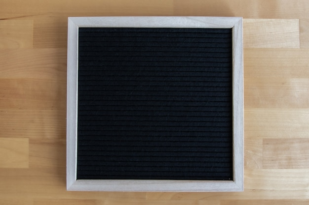 Vue de dessus d'un tableau vide noir sur une table en bois avec espace de copie pour vos devis