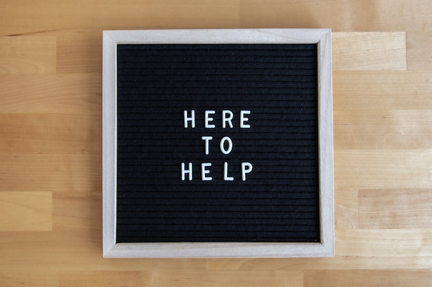 Vue de dessus d'un tableau vide noir sur une table en bois avec ici pour aider à citer