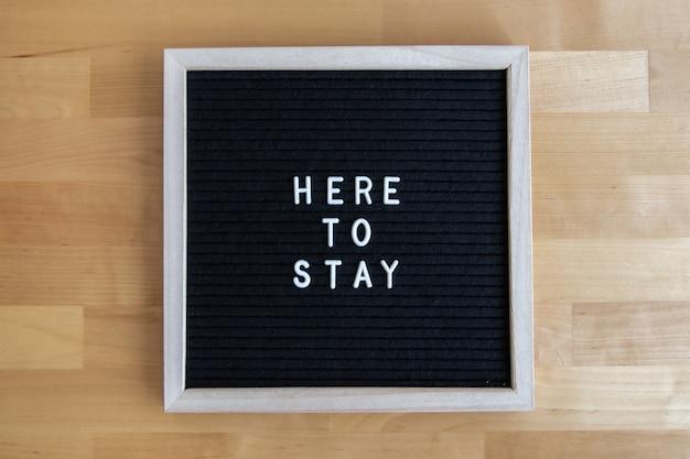 Vue de dessus d'un tableau vide noir sur une table en bois avec ici pour rester devis