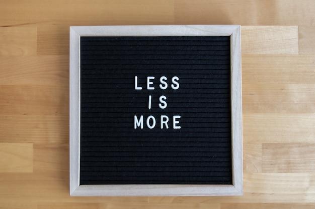 Vue de dessus d'un tableau vide noir sur une table en bois avec moins d'ir plus
