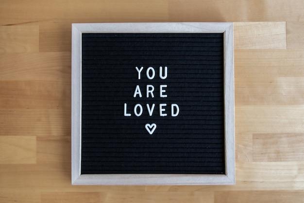 Vue de dessus d'un tableau vide noir sur une table en bois avec votre citation aimée
