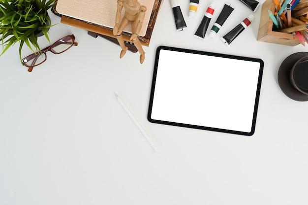Vue de dessus de la tablette avec écran blanc sur l'espace de travail de l'artiste ou du concepteur.