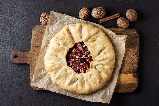 Vue de dessus tarte maison aux pommes, baies de sureau et noix sur planche de bois rustique