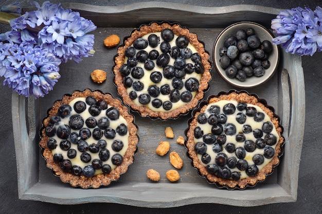 Vue de dessus sur les tartes aux bleuets entiers avec de la crème à la vanille sur dark