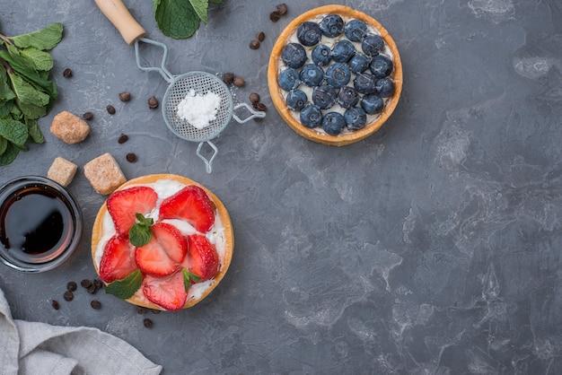 Vue de dessus des tartes aux fruits avec des fraises et des bleuets