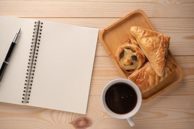 Vue de dessus des tartes et des desserts frais placés sur des plateaux en bois placés à côté d'un cahier vierge et des tasses à café blanches.