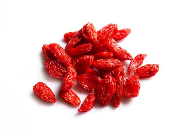 Vue de dessus tas de baies de goji rouges sur blanc.