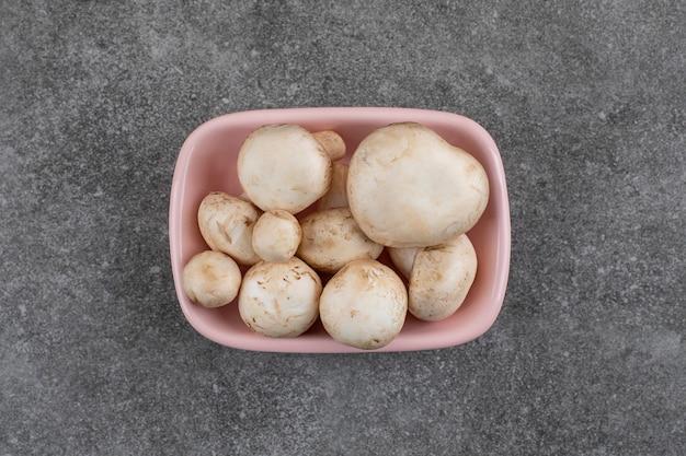 Vue de dessus. tas de champignons biologiques frais dans un bol rose