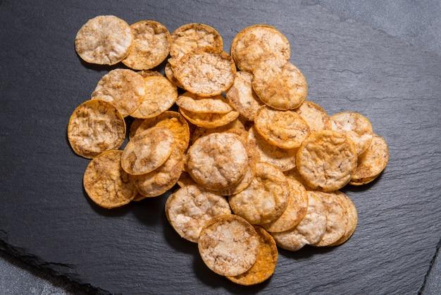 Vue de dessus tas de chips de riz bio, croustillant, cuit au four, à grains entiers avec des épices. collation saine sans gluten. sur une surface de pierre tranchée noire