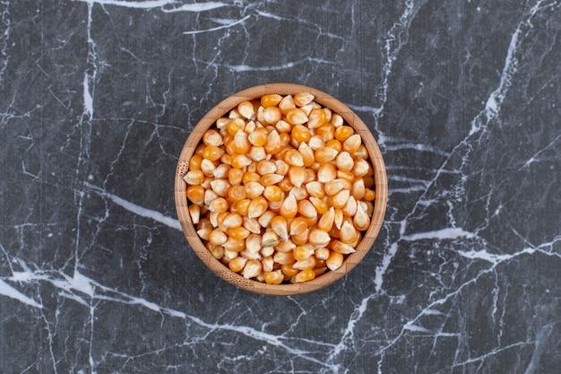 Vue de dessus. tas de graines de maïs dans un bol en bois.