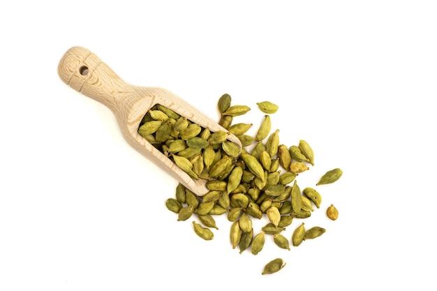 Vue de dessus sur tas isolé de graines de cardamome dans une cuillère en bois