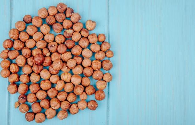 Vue de dessus d'un tas de noisettes pelées sur fond bleu avec copie espace