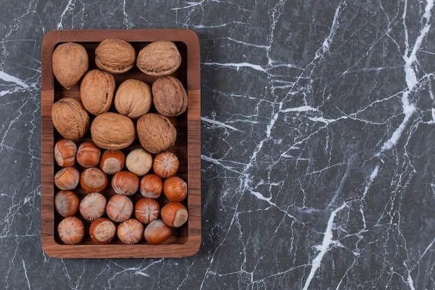 Vue de dessus. tas de noix et de noisettes sur une plaque en bois sur fond noir.