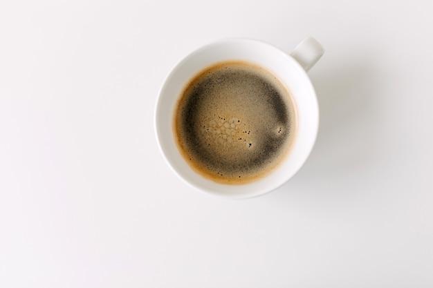 Vue de dessus d'une tasse blanche de café noir sur table blanche