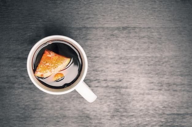 Vue de dessus sur la tasse blanche avec du vin chaud ou punch sur table en bois noir