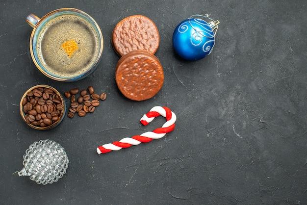 Vue de dessus une tasse de bol de café avec des graines de café et des biscuits détails de noël sur fond sombre isolé