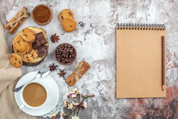 Vue de dessus tasse de bol de café avec grains de café torréfiés et cacao chocolat bâtons de cannelle biscuits cahier et crayon sur table