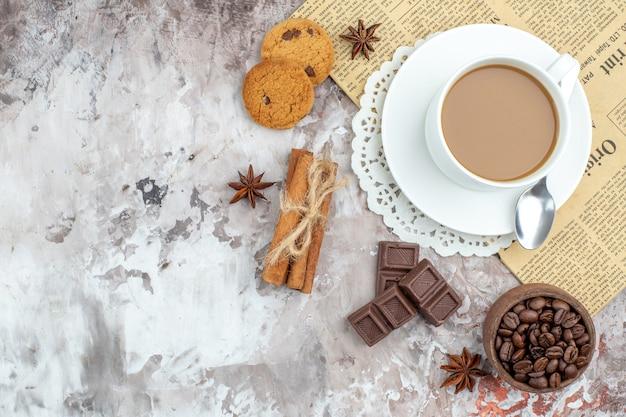 Vue de dessus tasse de bol de café avec des grains de café torréfiés chocolat bâtons de cannelle biscuits sur table avec copie place