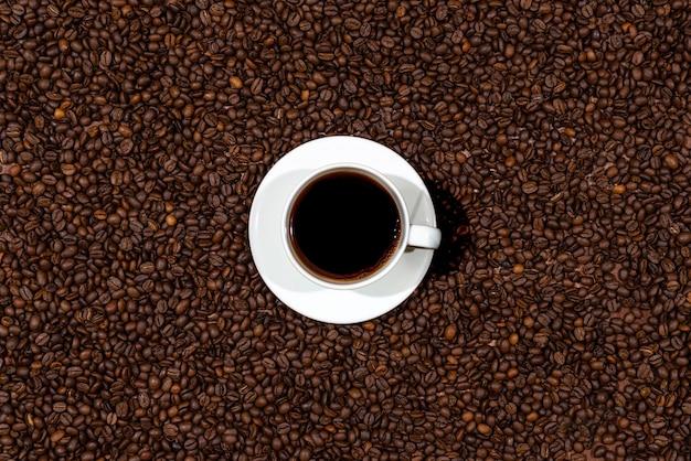 Vue de dessus de la tasse de café blanc sur le fond de grains de café