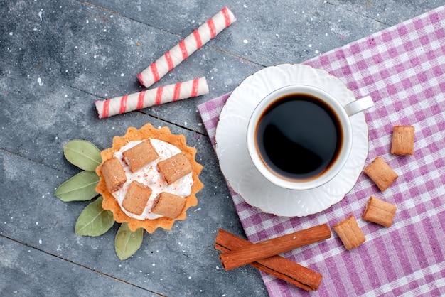 Vue de dessus de la tasse de café chaud et fort avec gâteau et cannelle sur gris, boisson sucrée de bonbons au café