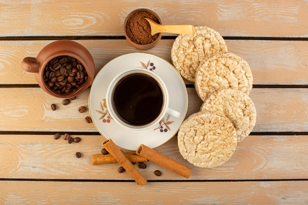Une vue de dessus une tasse de café chaud et fort avec des graines de café brun frais et des craquelins sur le bureau rustique crème café graine photo grain