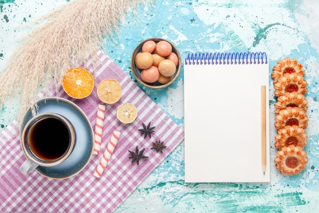 Vue de dessus tasse de café avec des cookies et bloc-notes sur fond bleu clair gâteau cuire biscuit tarte au sucre sucré