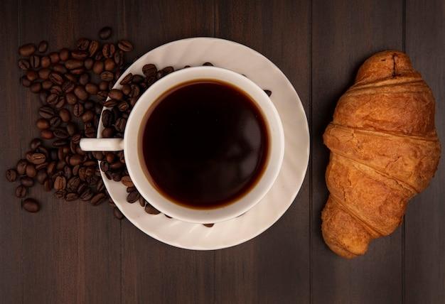 Vue de dessus d'une tasse de café avec un croissant avec des grains de café isolé sur un mur en bois