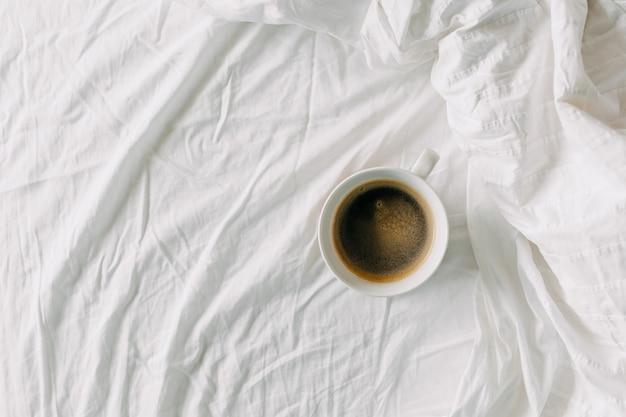 Vue de dessus d'une tasse de café sur un drap blanc petit-déjeuner au lit concept