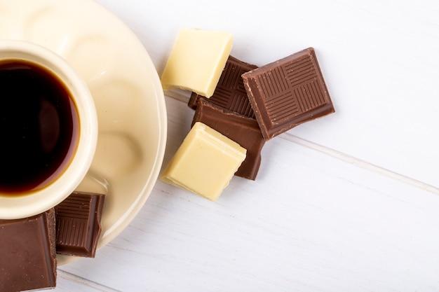 Vue de dessus d'une tasse de café avec du chocolat blanc et noir sur fond de bois blanc