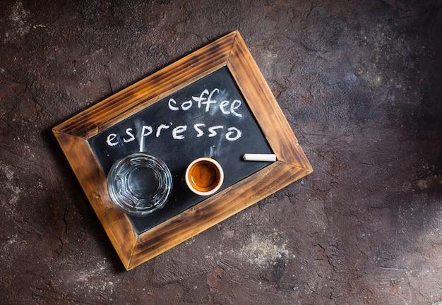 Vue de dessus d'une tasse de café et d'eau en verre sur une ardoise old school avec inscription